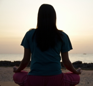 Meditating girl on beach